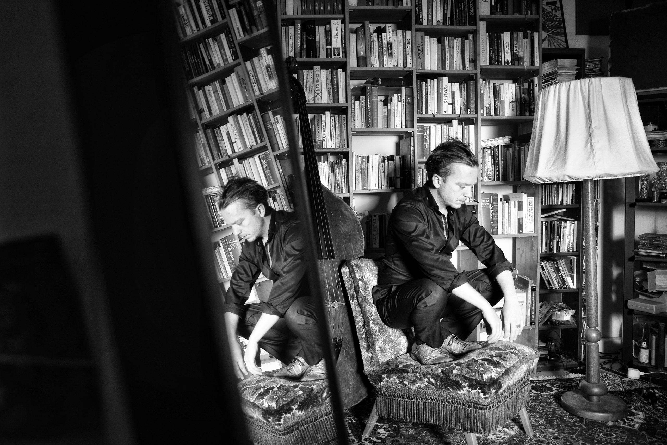 Peter Christof vor der Bücherwand